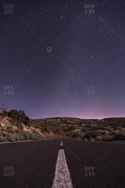 Empty road at night under bright stars
