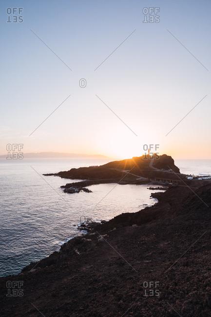 Scenic view of bright stunning sundown in clear sky illuminating empty remote coastline, Spain