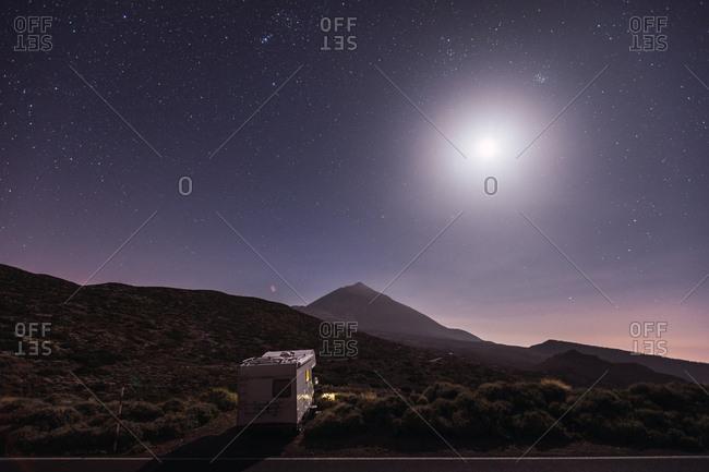 Traveling caravan in desert with bright moon