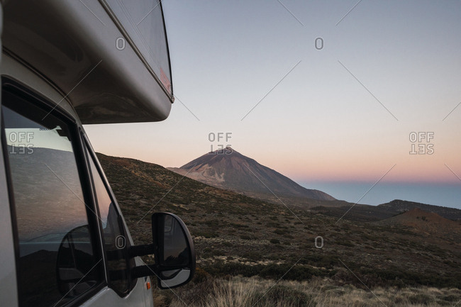 Camper parked in wild area on background of mountain peak and dawn sky in early morning