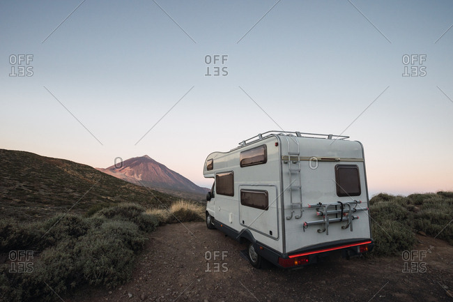 Caravan on roadside in desert landscape on background of beautiful mountain in dawn light