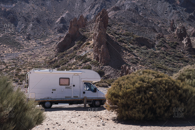 Traveling caravan on roadside in wild desert beside bushes on background of stony mountain in sunlight