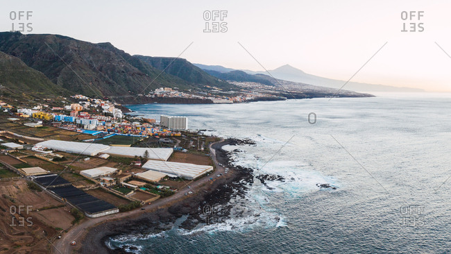 Aerial view of cityscape on majestic coastline at bottom of mountains of Tenerife, Spain