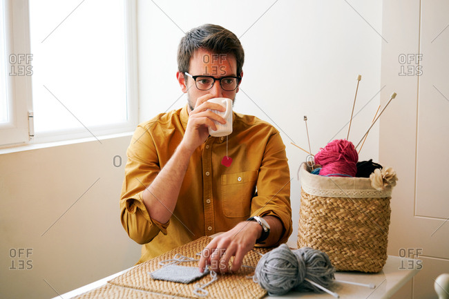 Adult male enjoying fresh hot tea and looking away while sitting at table near knitting needles and yarn