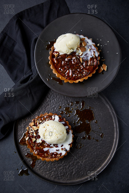 Two pecan pies with vanilla ice cream and chopped almonds on top.