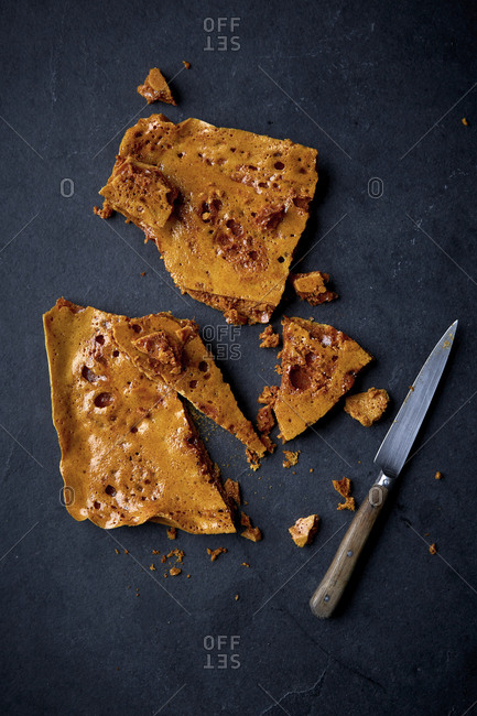 Shards of honeycomb candy with a knife on a black counter top.