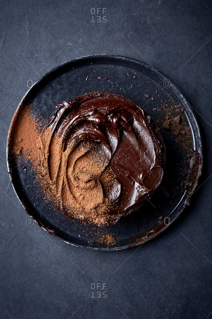 Chocolate cake with chocolate icing on a dark background.