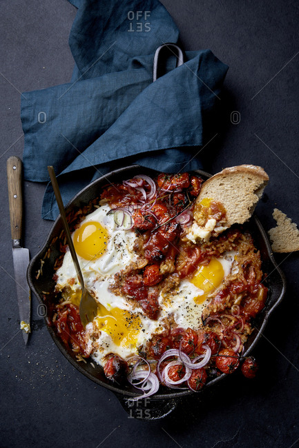 Eggs baked in rice with red onions and tomatoes on a black background.