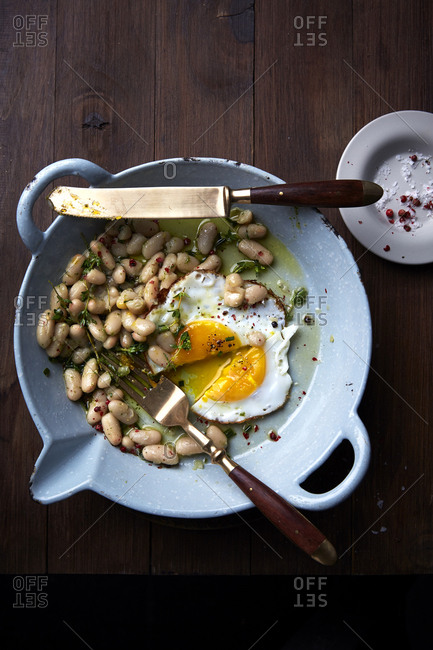 White beans with fried egg and knife and fork on a wooden tabletop.