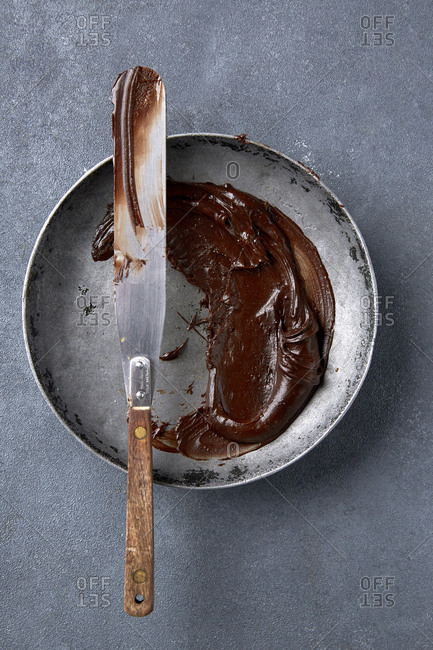 Chocolate icing in a bowl with a palette knife.