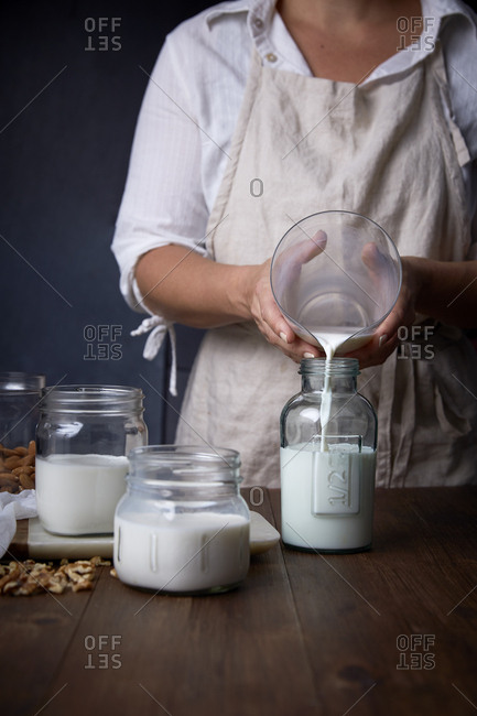 Person pouring nut milk into jars.