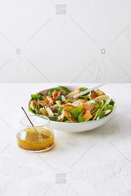 Bowl of apple cider vinegar salad with a side of dressing