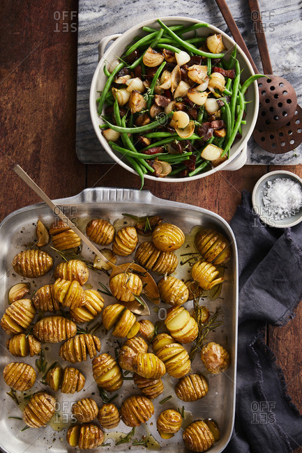 Hasselback potatoes served with a bowl of string beans