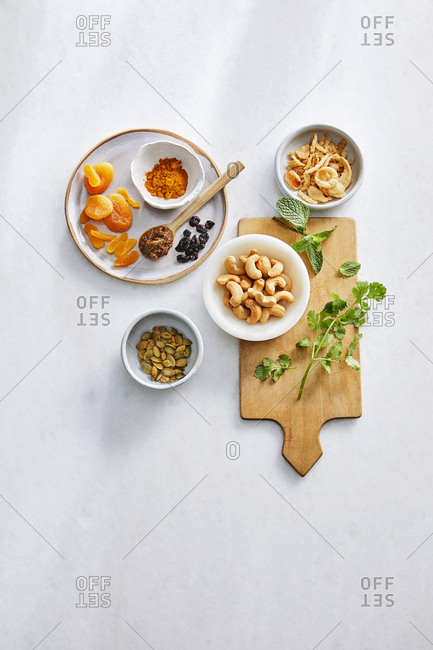 Overhead view of ingredients for chicken biryani on a white countertop