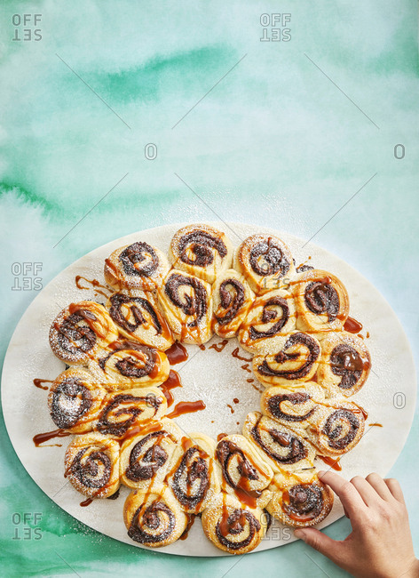 Overhead view of hand reaching towards chocolate hazelnut bread wreath