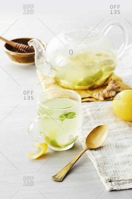 Hot ginger tea in a glass cup and tea pot set with a spoon.