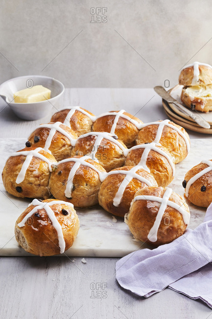 Fresh hot cross buns sitting on a marble cutting board accompanied by a dish of butter.