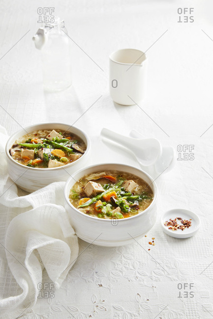 Two bowls of vegetable loaded hot and sour soup with tofu.
