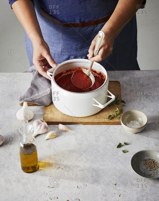 Woman preparing pasta sauce - Offset