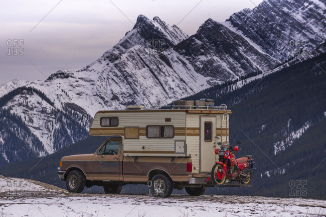 Camper Truck with Touring Motorcycle in front of mountain range sunset