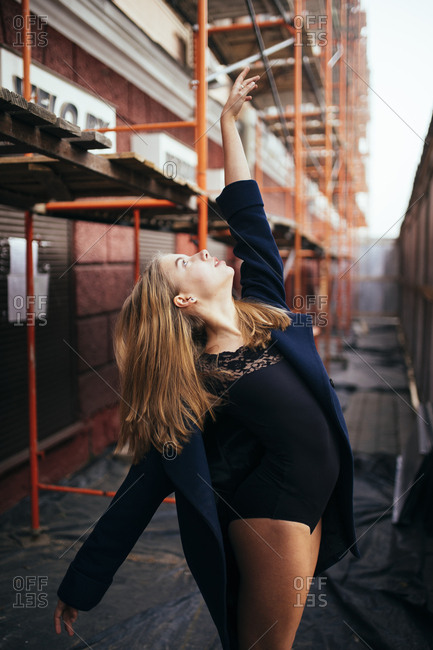 Woman ballerina stretching up near the scaffolding