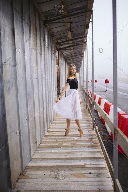 Woman ballerina in the city stands in the transition