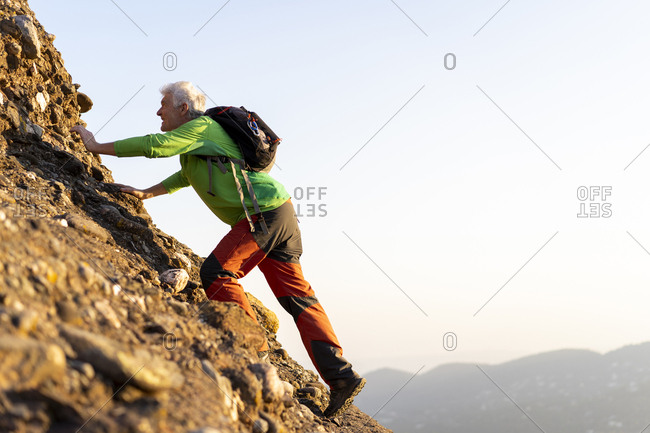 Senior man hiking a mountain during sunny day