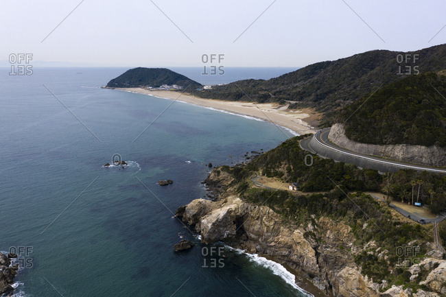Aerial view of winding road and beach by ocean
