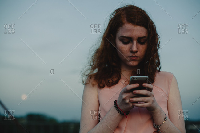 Young woman using smart phone while standing against sky at dusk