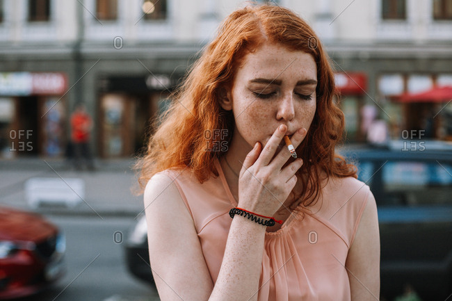 Young woman with freckles smoking cigarette while standing in street