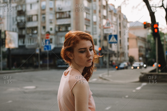 Portrait of young sad woman with freckles standing in city street