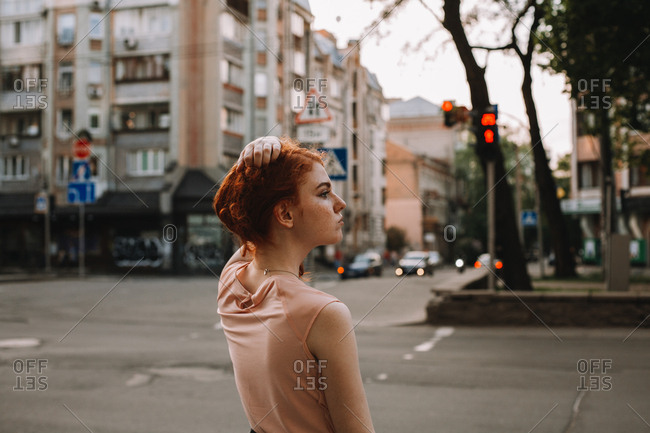 Young redheaded woman holding hair while standing in city street