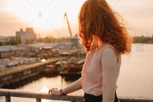 Young woman with red hair standing by railing on bridge at sunset