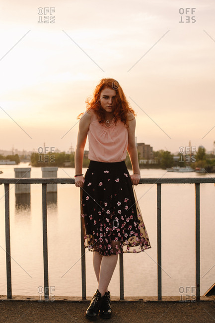 Full length portrait of young woman standing by railing on bridge