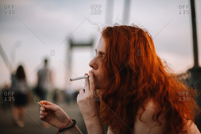 Young woman smoking cigarette while holding matchstick in hand