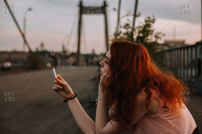 Young redhead woman holding cigarette in front of her face