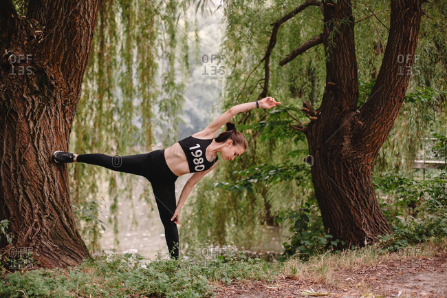 Sporty woman exercising on tree in park by lake
