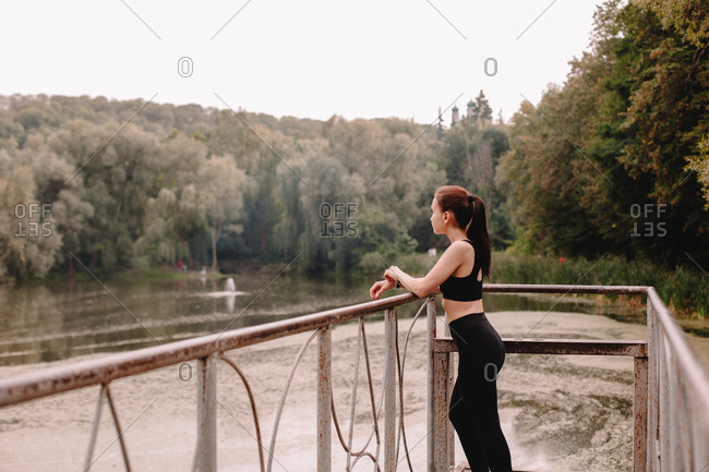 Thoughtful female jogger standing on pier by lake in park