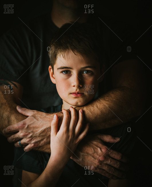 Close up portrait of serious boy with father's arms around him.