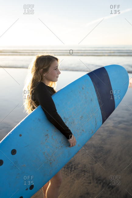 young surfer girl holding a blue surfboard