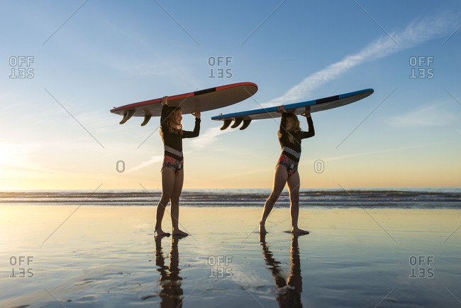 young surfer girls walking with surfboards on their head