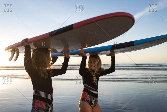 close up of sisters talking and walking with surfboards on their head