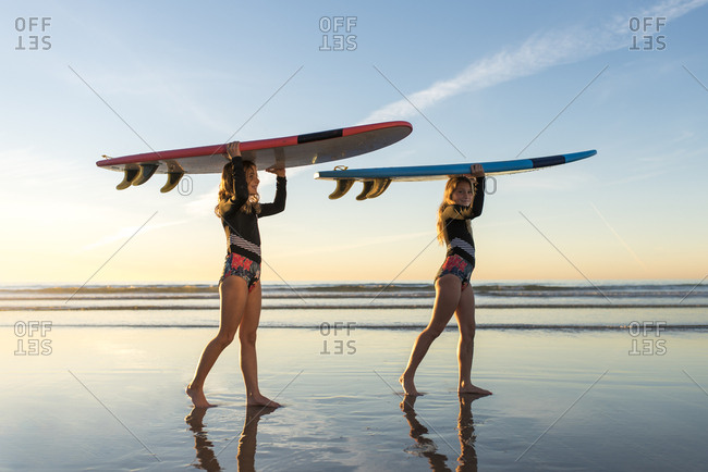 girls walking in matching swimsuits carrying surfboards on their head