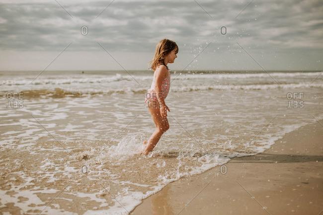 young girl wearing bathing suit splashing in the ocean