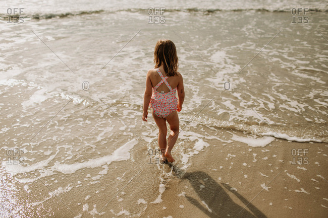young girl wearing bathing suit walking into the ocean