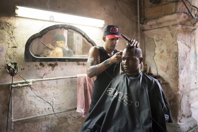 Havana, Cuba - May 2, 2016: A barber cuts a mans hair in an old building in Havana, Cuba.