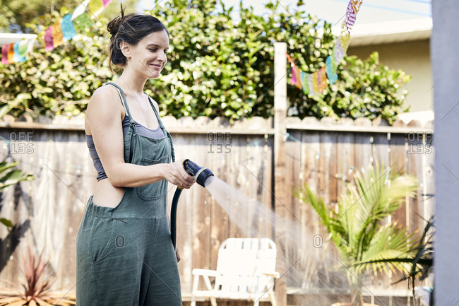 Smiling woman watering with hose at backyard