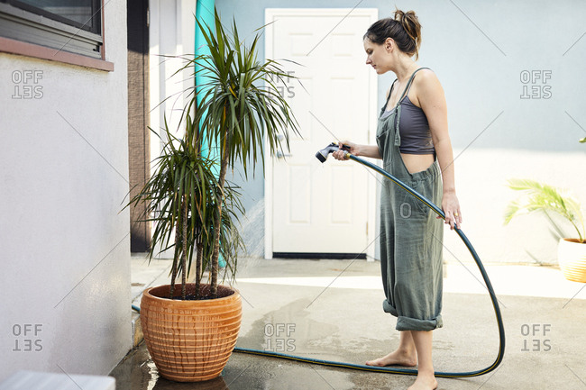 Side view of mid adult woman watering potted plant with hose at backyard