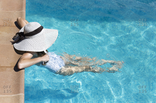 Unrecognizable woman relaxing in the swimming pool