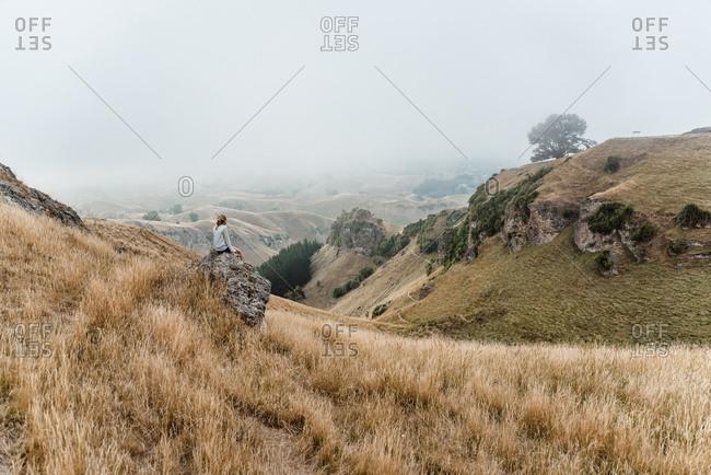 Girl sitting on rock on a hillside at Te Mata Peak